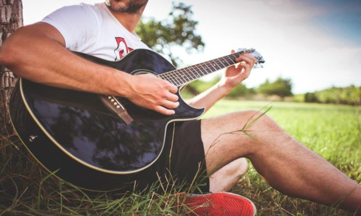 guy-playing-acoustic-guitar-in-nature-picjumbo-com